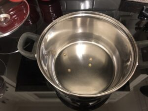 4 popcorn kernels in a pot with oil