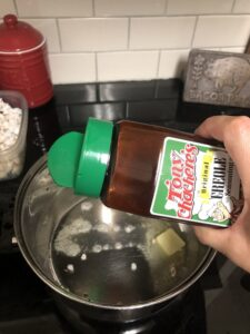Tony Chachere's Seasoning being added to melted butter for popcorn