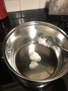 2 TBS of coconut oil being added to a pot