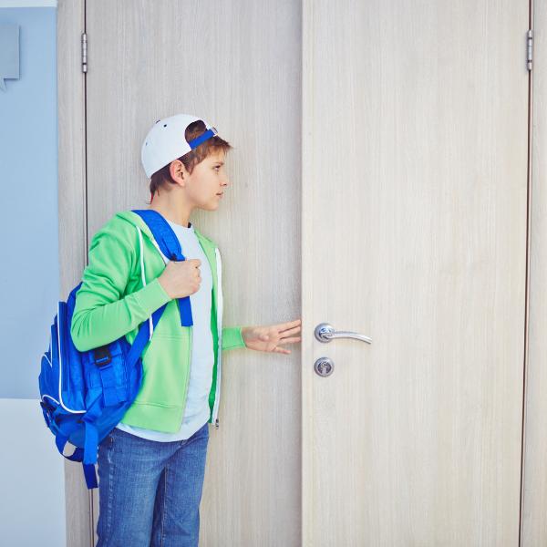 Male student opening classroom door