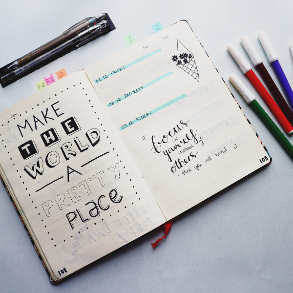 Opened Planner book with markers and pens