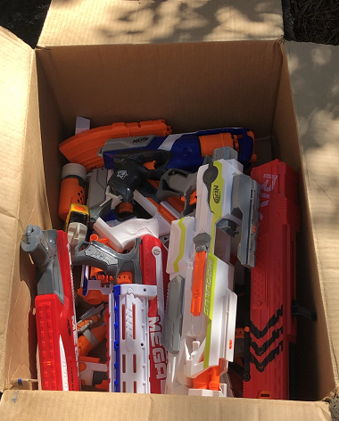 Open cardboard box with several Nerf Blasters