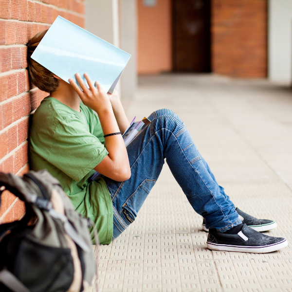 Student sitting against a wall with a book over his face